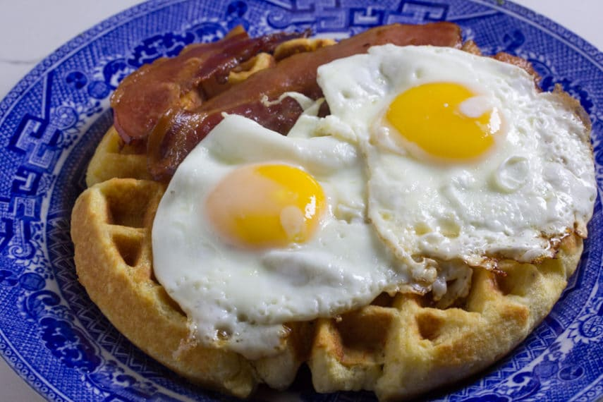 Two fried eggs and bacon on top of a low FODMAP Cornbread Waffle.