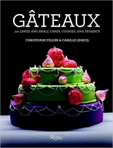 """front cover of the book """"Gateaux 150 large and small cakes, cookies, and desserts"""" with a brightly colored 3 tiered cake against a black background"""