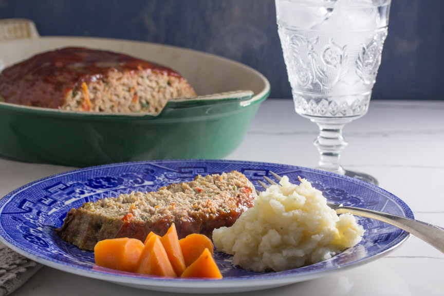 A slice of meatloaf served with mashed potatoes and carrots.