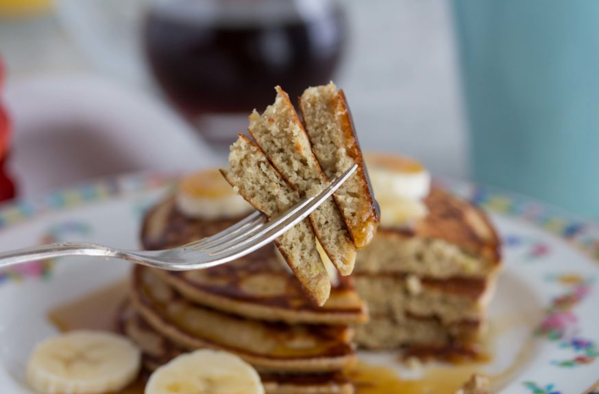 Fluffy quinoa pancakes stacked on a fork served with maple syrup and bananas.