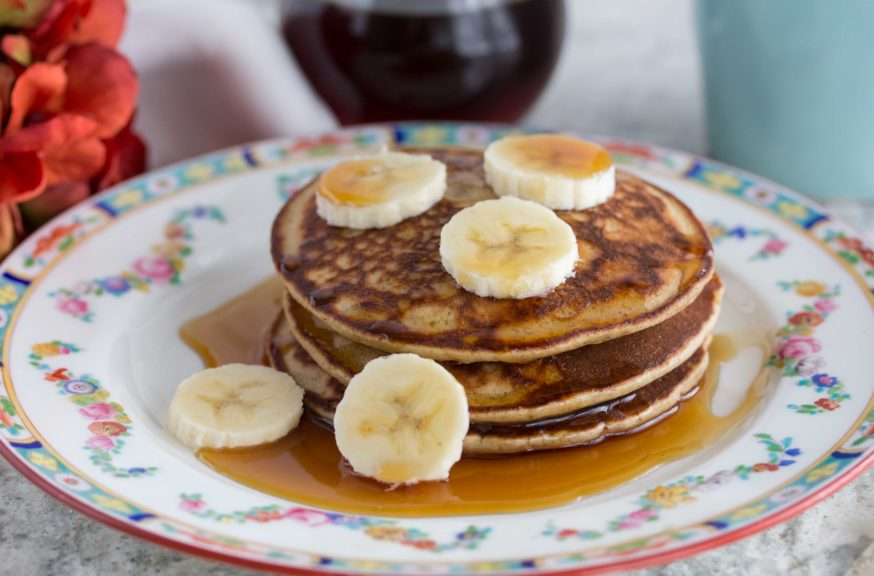 Sliced bananas with maple syrup poured over 3 stacked Quinoa Pancakes on a plate.