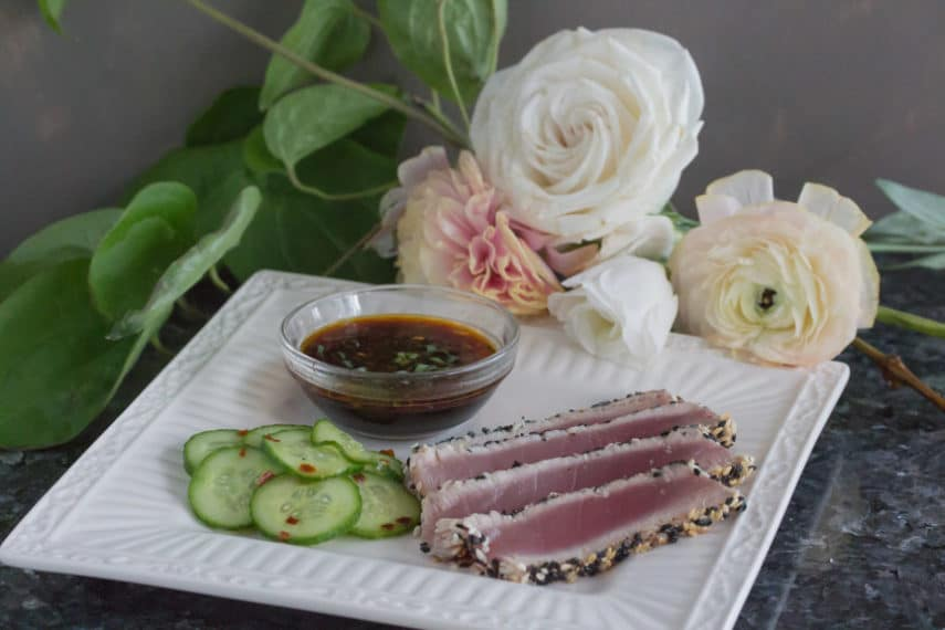 Low FODMAP Sesame Crusted Tuna & pickled cucumbers sliced and laid out on a white square plate with dipping sauce.