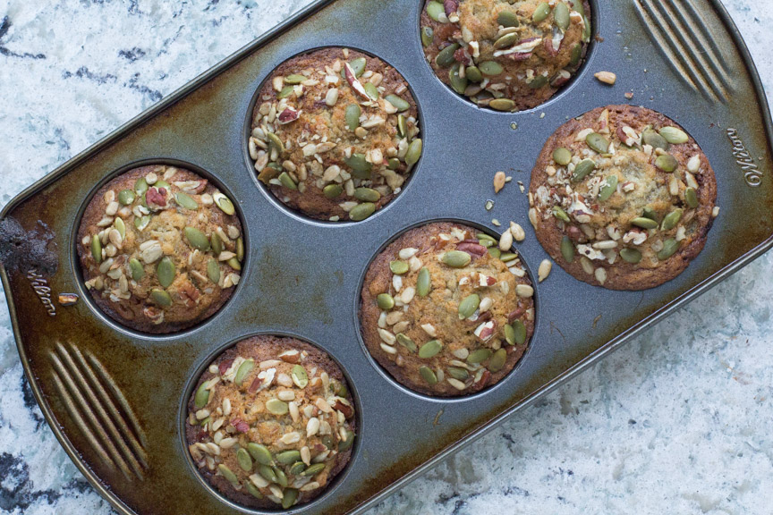 Low FODMAP Banana muffins in a muffin tin- covered in nuts and seeds for crunch!