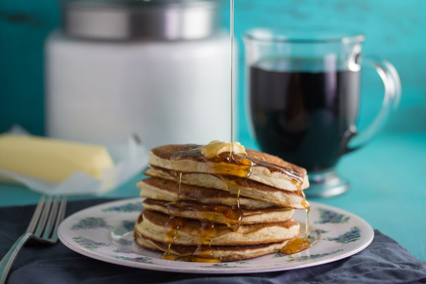 Low FODMAP buttermilk oat pancakes and coffee against an aqua background