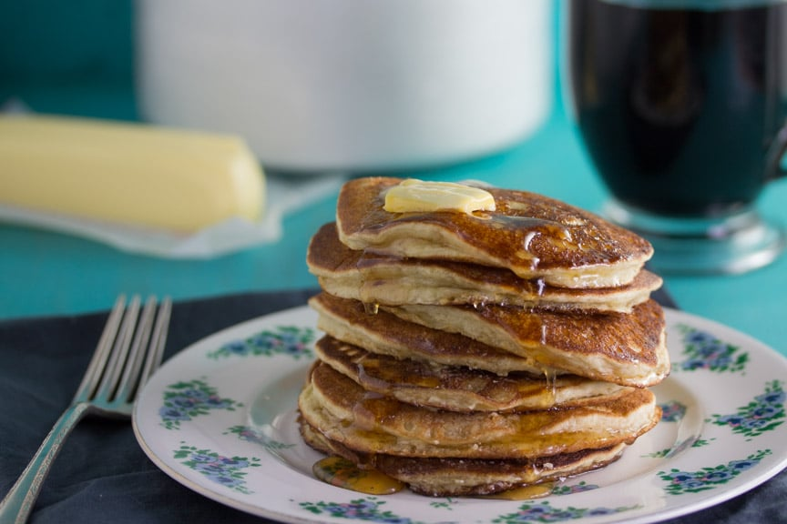 Stack of Low FODMAP Buttermilk Oat Pancakes with butter and syrup poured over the top