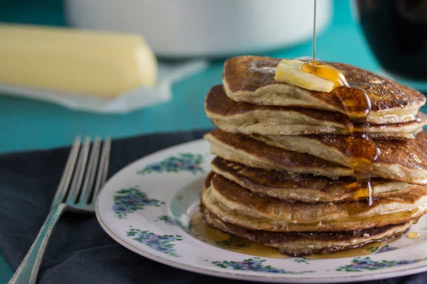 Stack of Low FODMAP Buttermilk Oat Pancakes with butter and syrup being poured over the top
