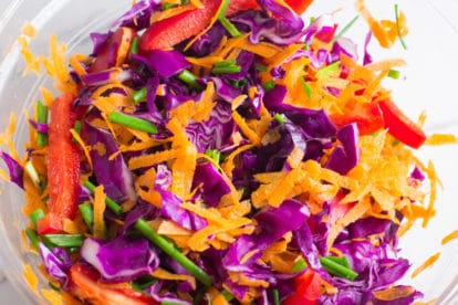 A bowl of brightly colored fresh salad vegetables.