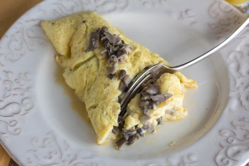 fork cutting into a low FODMAP mushroom omelet on white plate