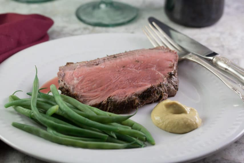 A slice of rare roast beef served on a white plate with green beans and mustard.