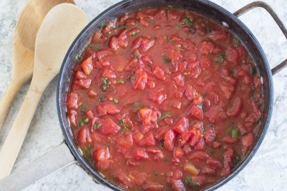Super Simple Chunky Tomato Sauce in black saucepan, cans of tomatoes in background