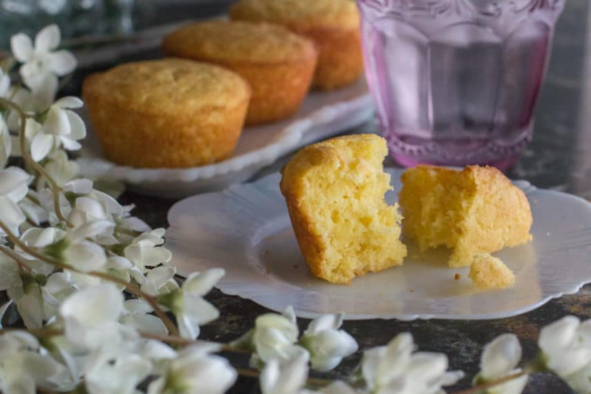Low FODMAP corn muffin - perfectly moist, slightly sweet, and with the perfect crumble - cut open on a plate.