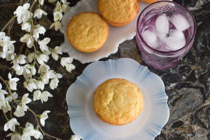Low FODMAP cornbread muffins - viewed from above accompanied by a glass of ice water.