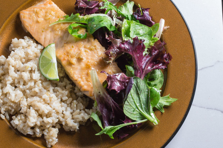 miso lime glazed salmon served alongside a salad and brown rice