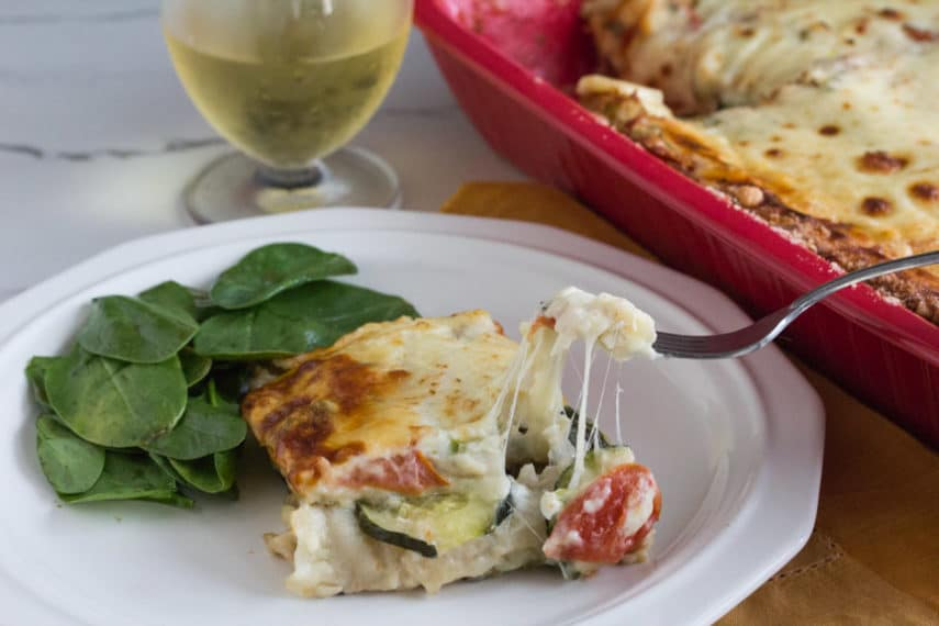 A forkful of low FODMAP summer vegetable white lasagne with gooey cheese.