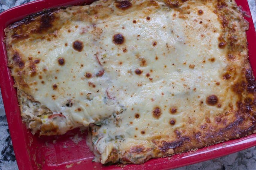 Summer vegetable white lasagne fills a red deep baking dish.