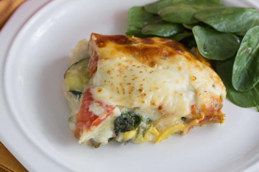 A slice of summer vegetable white lasagne served with a spinach salad.