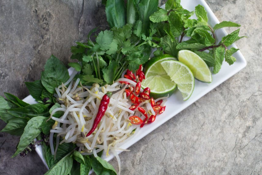 A plate full of Pho Bo garnishes- bean sprouts, limes, mint, cilantro and cayenne peppers.