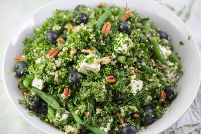 Low FODMAP kale blueberry feta salad tossed together in a bowl makes for a delicious and festive addition to any meal