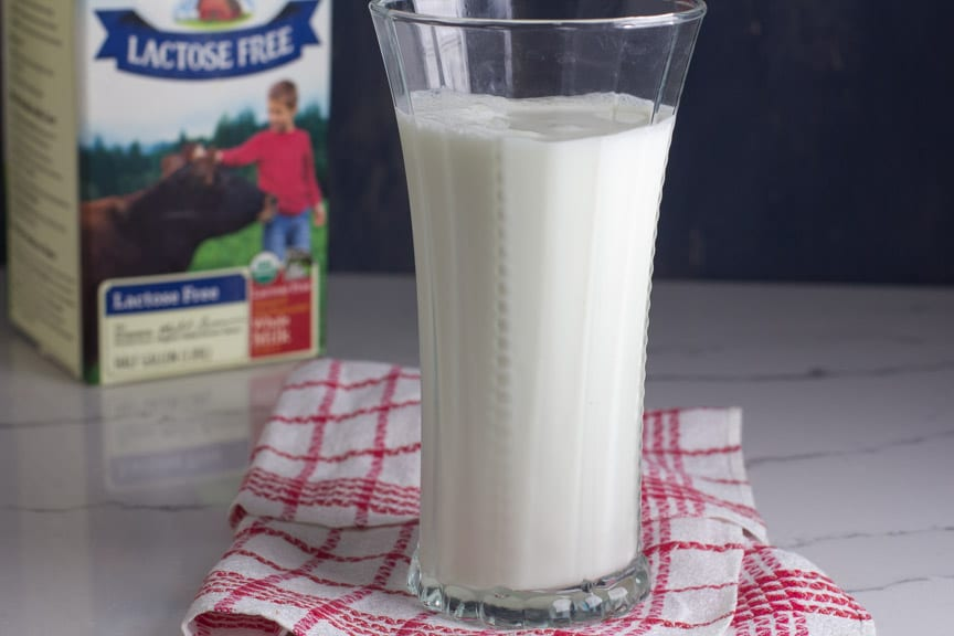 A tall glass of lactose free milk in front of Organic Valley Lactose Free Milk container
