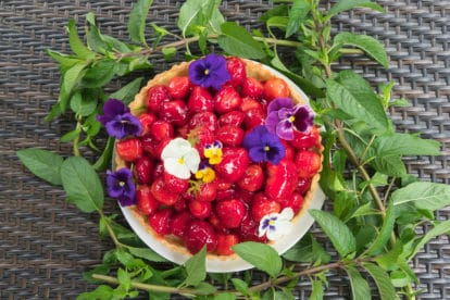 A vibrant fresh strawberry glazed tart, with pansies surrounded chocolate mint.