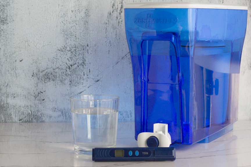 ZeroWater filtration system - large blue filtration water tank, glass of filtered water and tester.