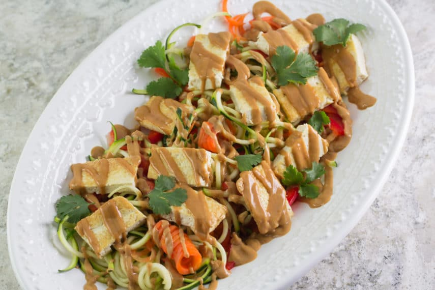 Zoodles & Tofu with peanut sauce on a white platter. A Monash University Certified Low FODMAP Recipe.