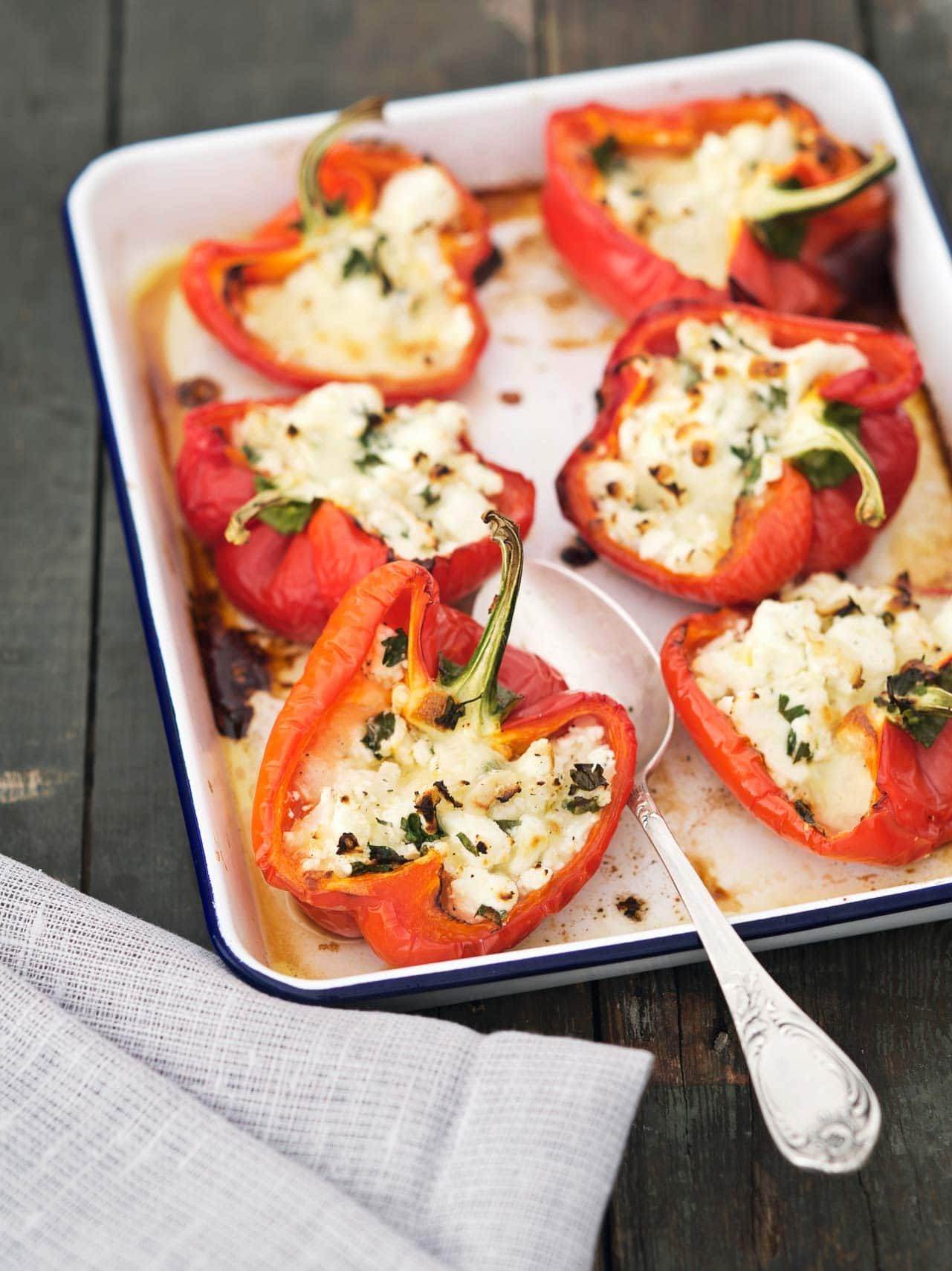 Stuffed Red Peppers in a white baking dish with spoon