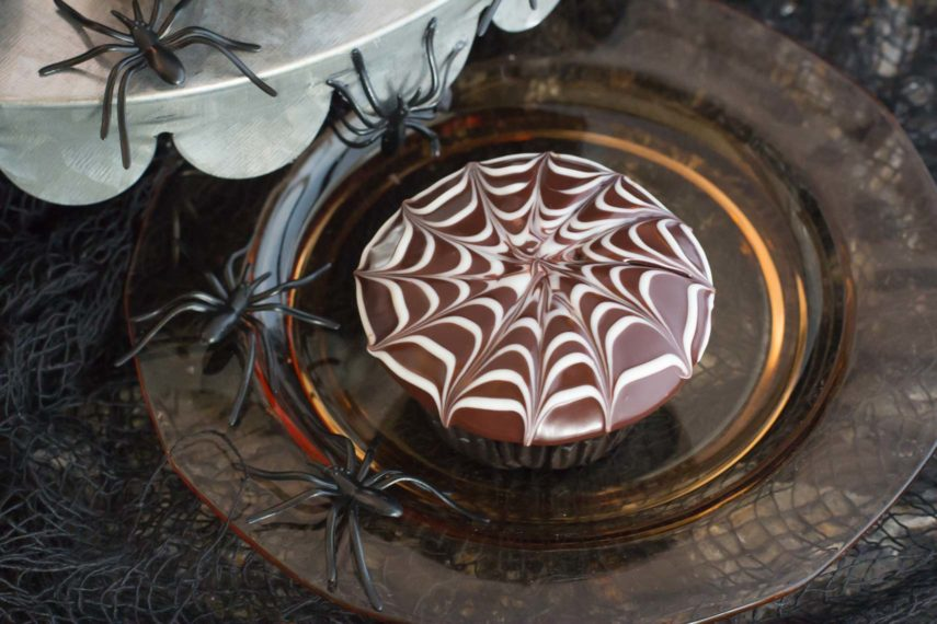 A spider web decorated chocolate cupcake surrounded by spiders. For a delicious Low FODMAP Halloween treat.