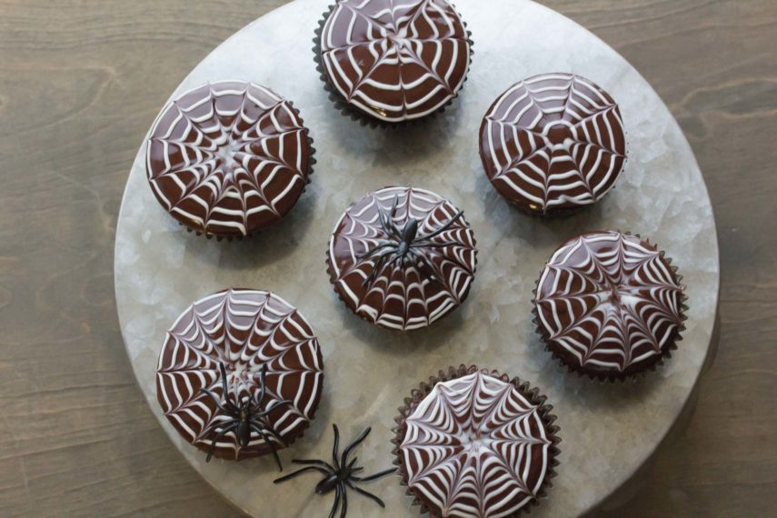 An overhead view of 7 spiderweb decorated chocolate cupcakes on a tin platter.
