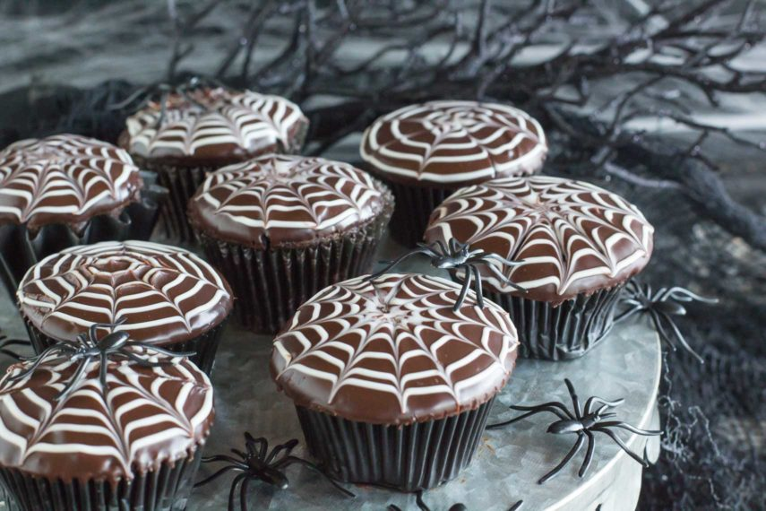 A plateful of spiderweb decorated chocolate cupcakes with spiders crawling all over them! Boo!