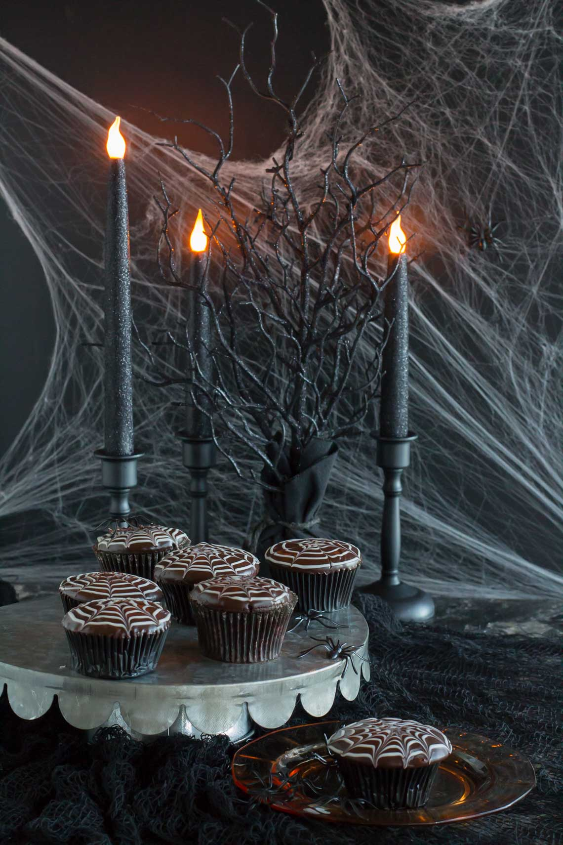 The perfect Halloween setting- black lit candles in black candelabras surrounded by spiderwebs and black tree branches- with a plate of spiderweb decorated chocolate cupcakes to chase away the goblins.