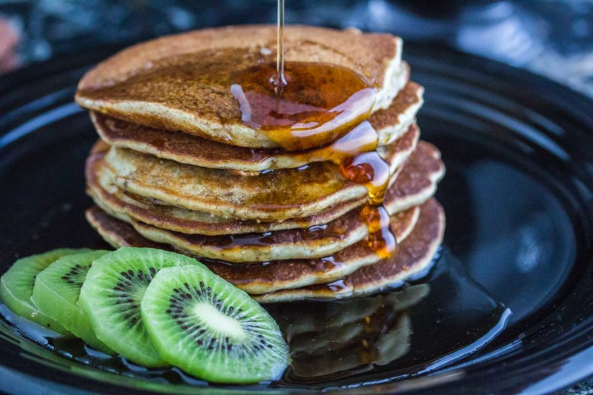 3 Seed dairy-free gluten-free Pancakes closeup on dark plate with kiwi alongside
