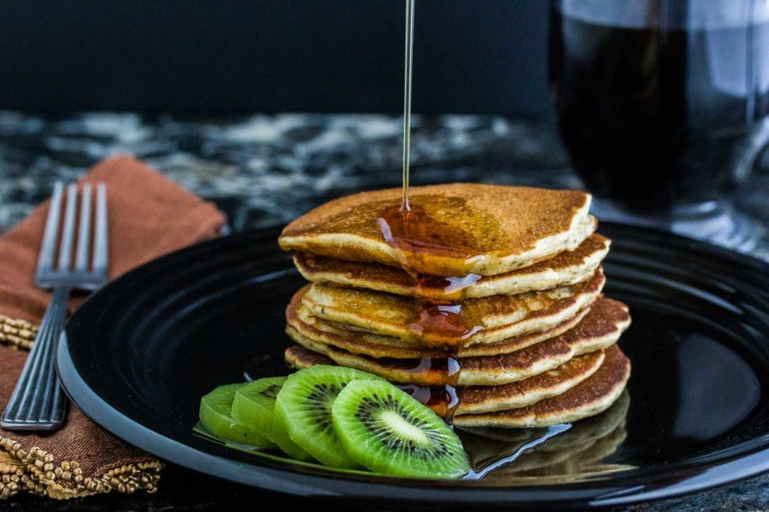Maple syrup being poured over 3 Seed dairy-free gluten-free Pancakes on a plate served with sliced kiwi.