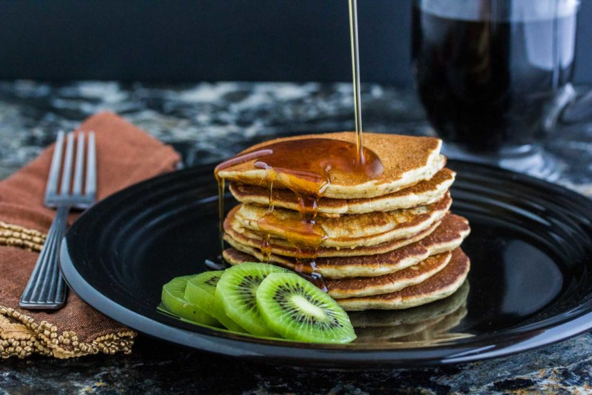 Maple syrup being poured over 3 Seed dairy-free gluten-free Pancakes on a plate served with sliced kiwi. With a slice taken out.