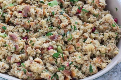 Cornbread bacon stuffing with pomegranate in an oval white casserole dish