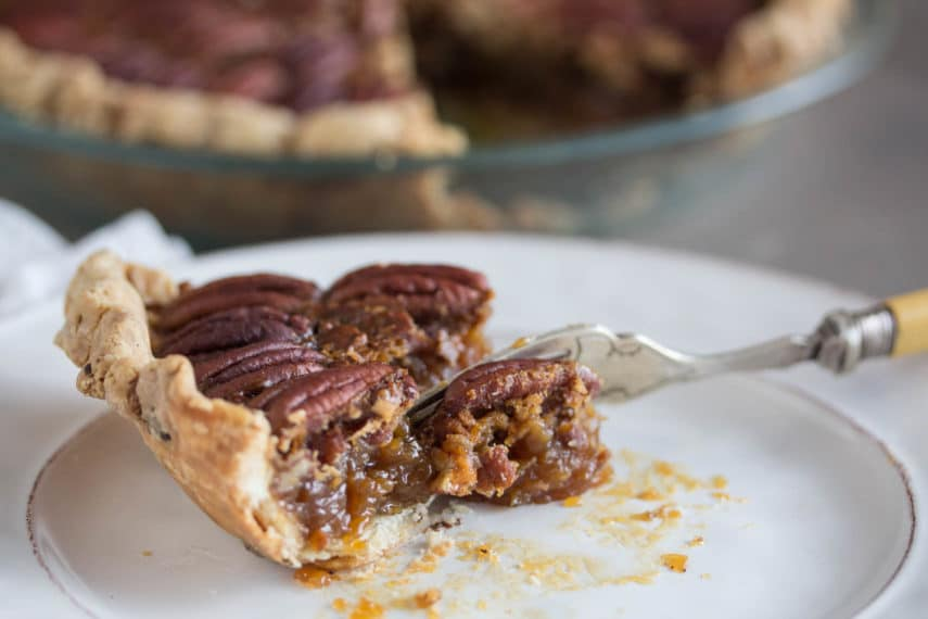 A slice of Browned Butter Salted Caramel Pecan Pie in a chocolate flecked pastry crust