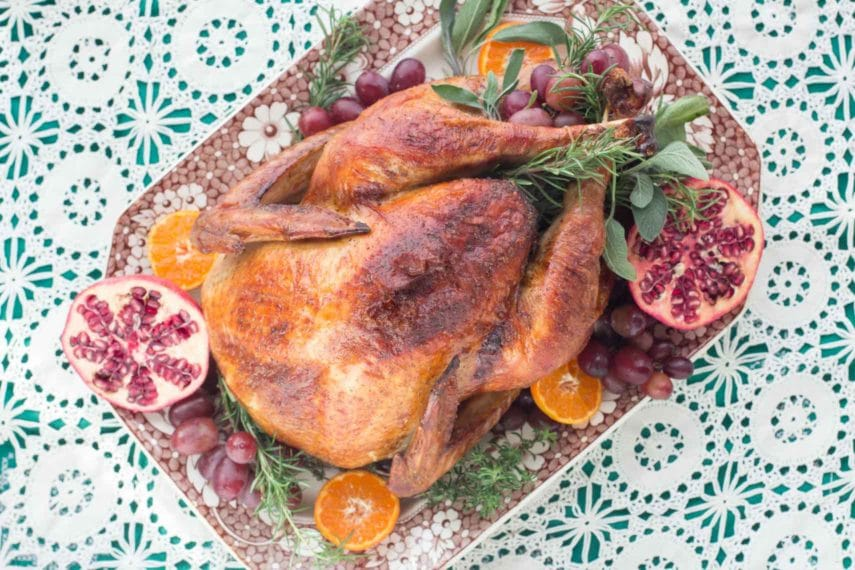 A gorgeously roasted Beer & Brown Sugar brined turkey seen from overhead - on a platter with pomegranates and oranges.
