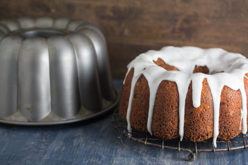 Cranberry Almond Buttermilk Bundt Cake glazed on a rack, next to Bundt pan