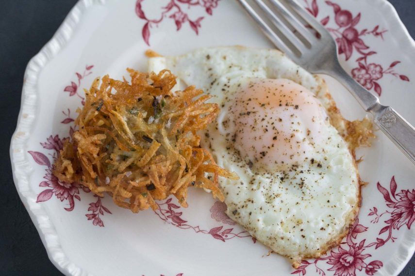 fried egg with latke on a red and white antique plate