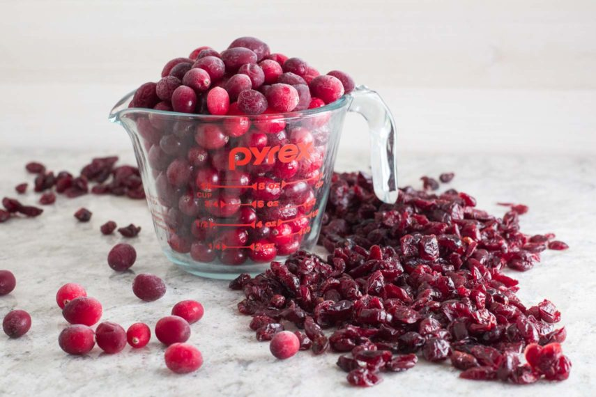frozen cranberries in a measuring cup with dried cranberries alongside