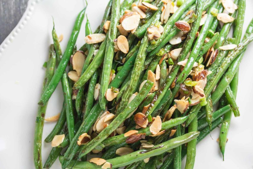 pan-roasted green beans topped with toasted almonds on an oval white platter