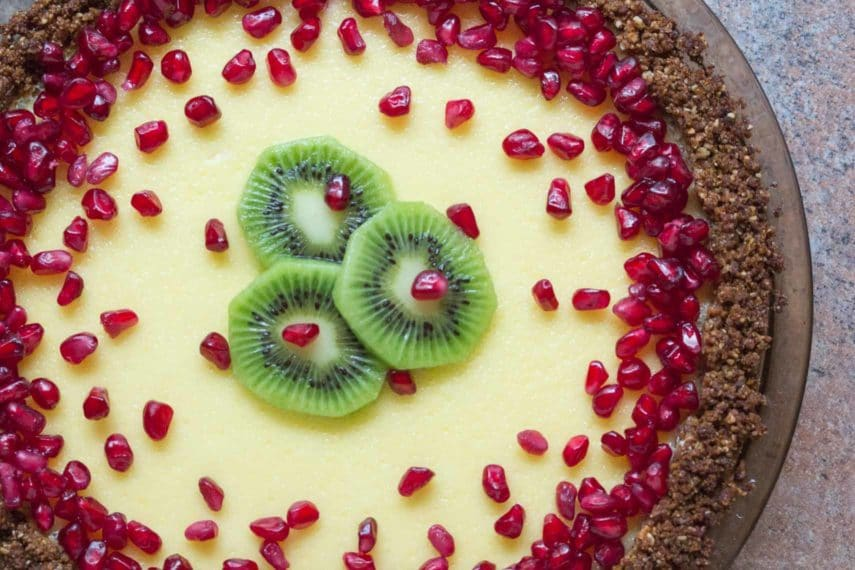 lactose free cheesecake pie in a pat-in crust topped with pomegranate and kiwi