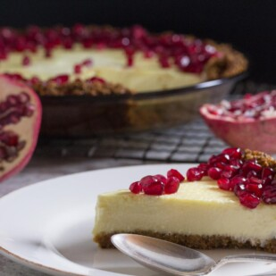 lactose free cheesecake pie in a pat-in crust topped with pomegranate with whole pie in background and slice on a plate in the foreground