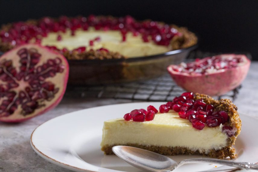 lactose-free cheesecake pie in a pat-in crust topped with pomegranate with whole pie in background and slice on a plate in the foreground