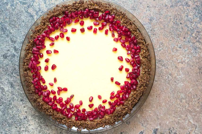 lactose-free cheesecake pie in a pat-in crust topped with pomegranate_