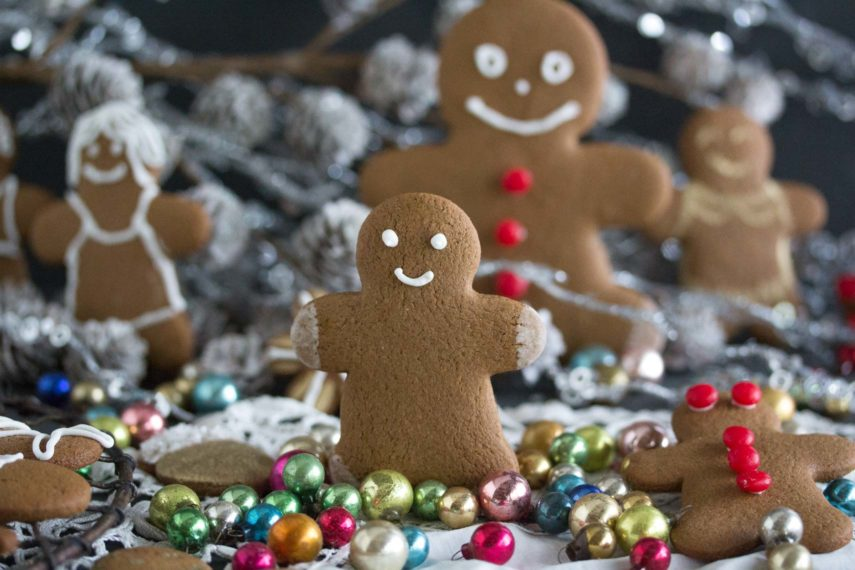 little gingerbread boy decorated with royal icing standing up amidst cookies and ornaments