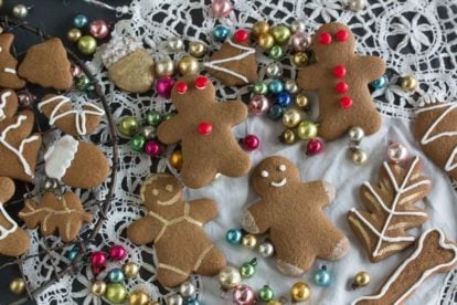 overhead shot of gingerbread cookies decorated with red hot candies and icing and edible gold paint on an antique clot