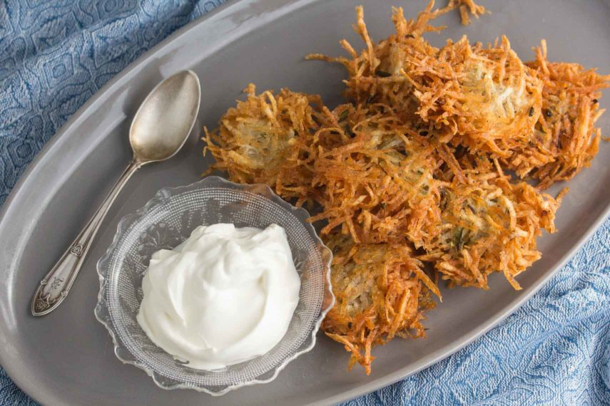 overhead shot of crisp potato latke on a grey platter with lactose-free sour cream