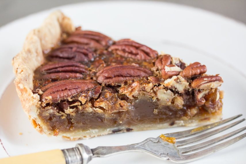 slice of pecan pie on a plate with a fork