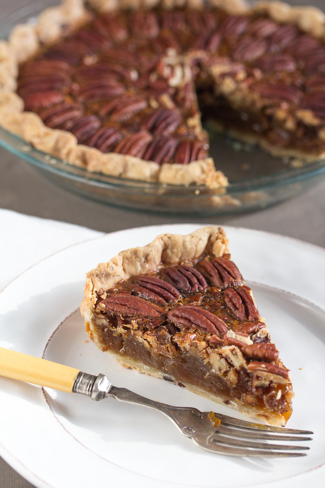 vertical image of a pecan pie with a slice on a plate in the foreground